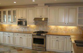 white kitchen with granite tops and backsplash